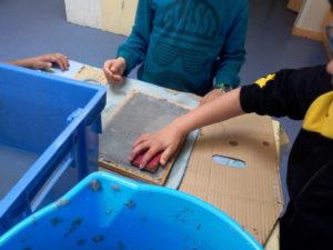Les enfants en train de filtrer leur papier avec l'éponge..